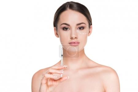 beautiful young woman with dotted line drawn on face for plastic surgery holding syringe isolated on white
