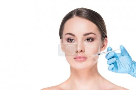 beautiful young woman with dotted line drawn on face for plastic surgery taking beauty injection isolated on white