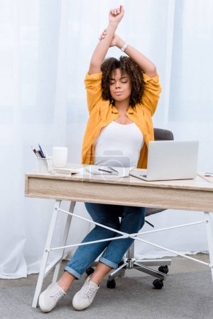 tired young woman stretching at workplace
