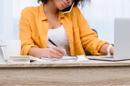 cropped shot of young woman working with laptop and notebook while talking by phone