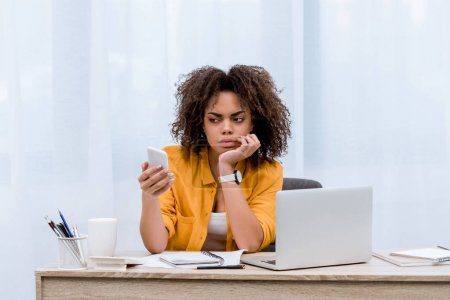 suspecting young woman looking at smartphone at workplace