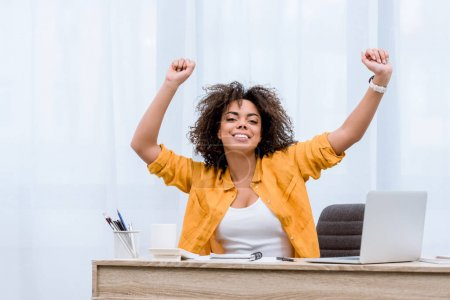 beautiful young woman performing victory dance at workplace