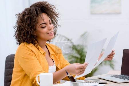 Photo pour Femme jeune métisse, faire de la paperasse au bureau - image libre de droit