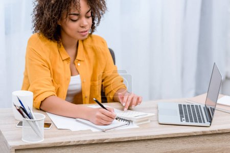Photo for Beautiful young woman working with laptop and writing in notebook - Royalty Free Image