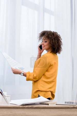 happy woman with business papers talking by phone