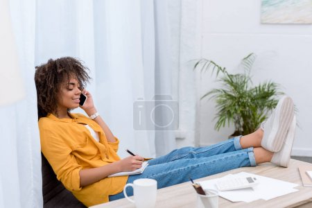 beautiful young woman talking by phone and writing in notebook