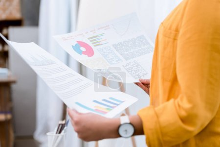cropped shot of woman with business papers with graphs