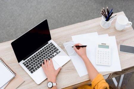 Photo pour Recadrée coup de jeune femme travaillant avec ordinateur portable au bureau - image libre de droit