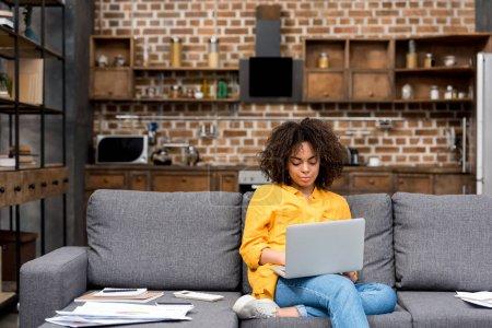 Photo pour Attrayant jeune femme travaillant avec ordinateur portable sur le canapé - image libre de droit