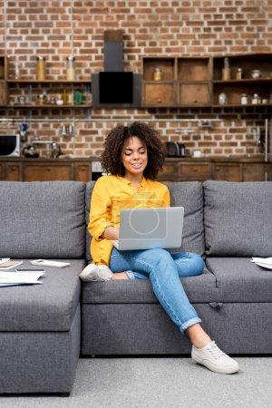 Photo pour Belle femme de race mixte travaillant avec ordinateur portable sur le canapé - image libre de droit