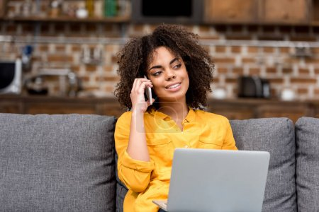 young woman working and talking by phone at home on couch