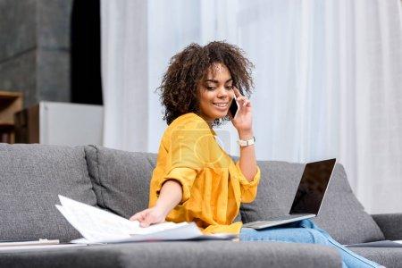Photo pour Heureuse jeune femme travaillant et parlant par téléphone à la maison sur le canapé - image libre de droit