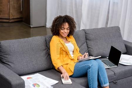 Photo pour Attrayant afro-américain femme travaillant avec calculatrice à la maison sur le canapé - image libre de droit
