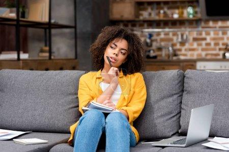 Foto de Mujer joven reflexiva trabajo en casa en el sofá - Imagen libre de derechos