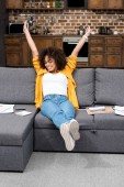 beautiful african american woman working at home and stretching on couch