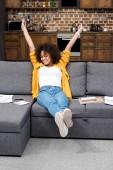 belle femme afro-américaine, travailler à la maison et qui s'étend sur canapé