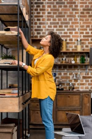 beautiful young woman taking book from shelf at home