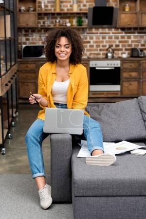 Photo for Beautiful young woman working with laptop on couch at home - Royalty Free Image