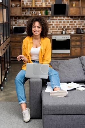 Photo pour Belle jeune femme travaillant avec portable sur canapé à la maison - image libre de droit