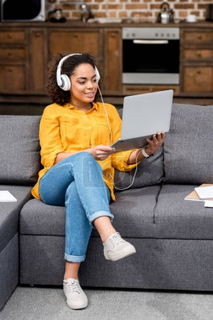 smiling young woman working with laptop and listening music at home