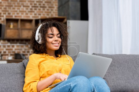 happy young woman working with laptop and listening music at home
