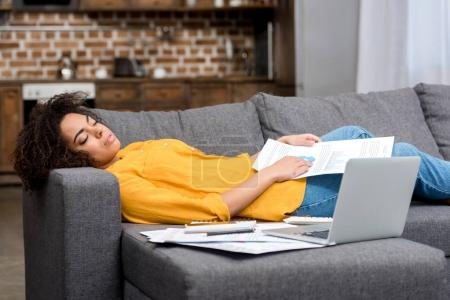 tired african american woman sleeping on couch after work at home