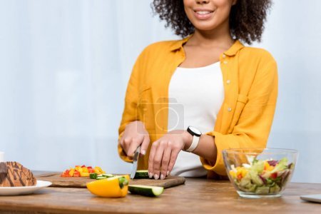 Photo for Cropped shot of smiling woman slicing vegetables for salad - Royalty Free Image