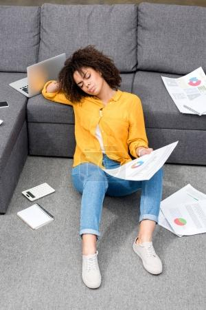 beautiful young woman sitting on floor at home and doing paperwork