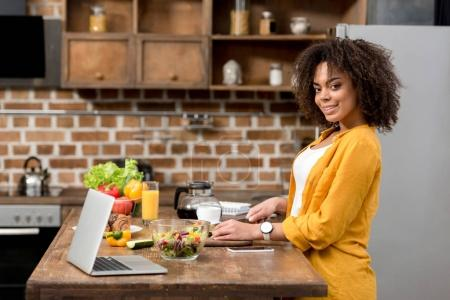 Photo for Side view of beautiful young woman slicing vegetables for salad - Royalty Free Image