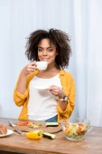young  mixed race woman drinking coffee and taking diner at home