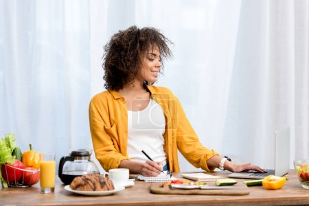 beautiful young woman working with laptop while taking meal