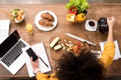 top view of young woman smartphone at kitchen with various food and laptop on table and pouring coffee into cup