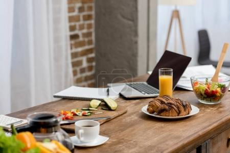 freelancer workplace at kitchen with food on table and laptop