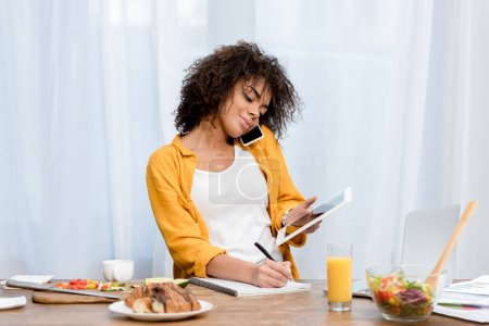 young african american woman working at home during breakfast