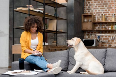 Photo pour Séduisante jeune femme travaillant avec ordinateur portable à la maison avec son chien - image libre de droit