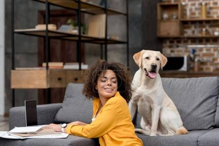 beautiful young woman working with laptop at home while her dog sitting on couch