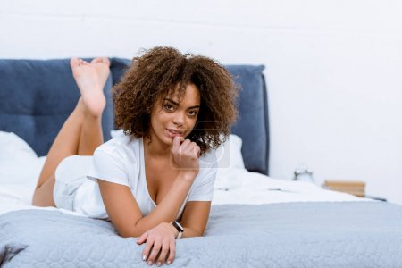 beautiful young woman lying on bed and looking at camera