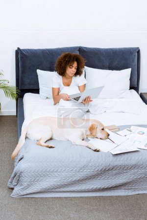 african american woman working with laptop on bed with her dog