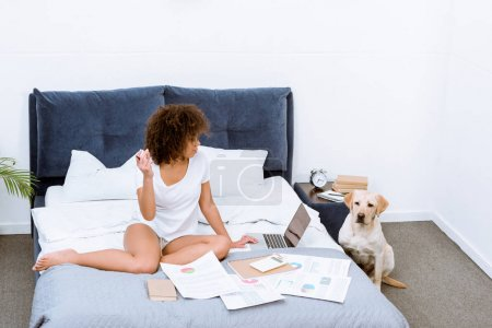attractive woman working with laptop on bed with her dog