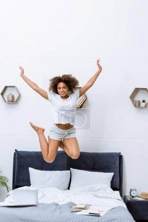 happy young african american woman jumping on bed at home