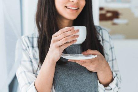 Photo pour Femme afro-américaine souriante buvant du café dans une tasse blanche - image libre de droit