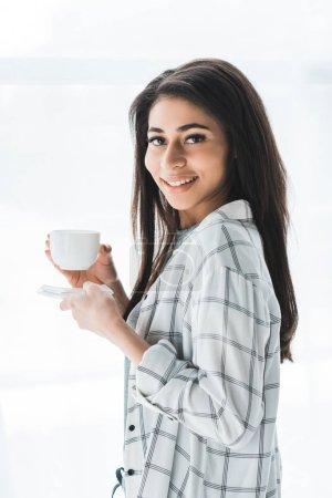 Photo pour Souriant femme attrayante tenant tasse de café - image libre de droit