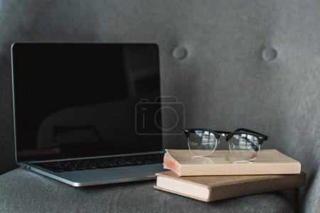 Laptop with empty screen and books lying on grey chair