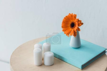 Gerbera flower and candles on wooden table