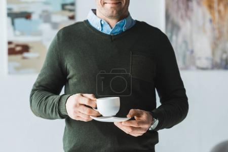 Smiling man holding cup of coffee in his hands