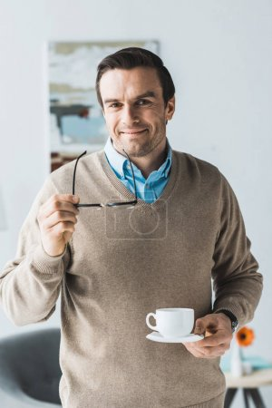 Attractive man holding glasses and cup of coffee