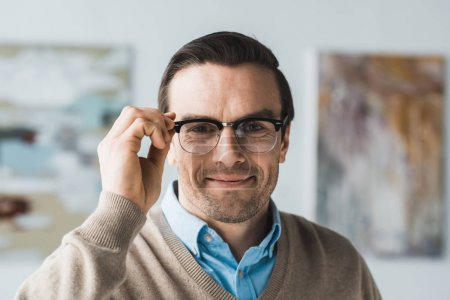 Smiling adult man fixing his eyeglasses