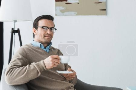 Smiling man in glasses sitting in chair and drinking coffee