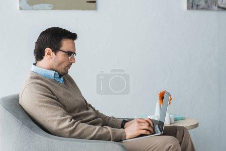 Photo pour Homme confiant dans des verres en tapant sur le clavier d'ordinateur portable - image libre de droit