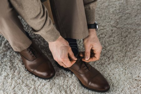 Photo for Close-up view of man tying shoelaces of his leather shoes - Royalty Free Image